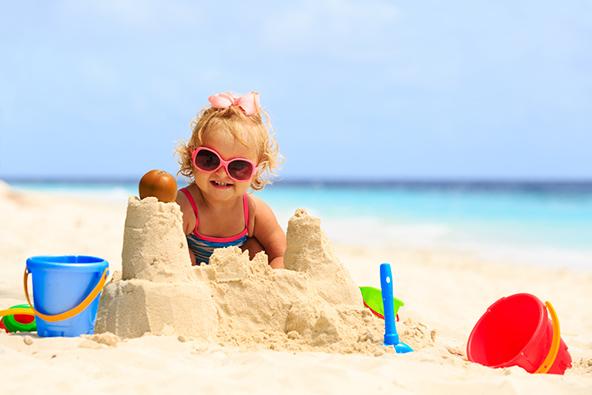 פעוטה על חוף הים. תינוקות וילדים צעירים מאוד לא זקוקים לאטרקציות מיוחדות כדי ליהנות בחופשה