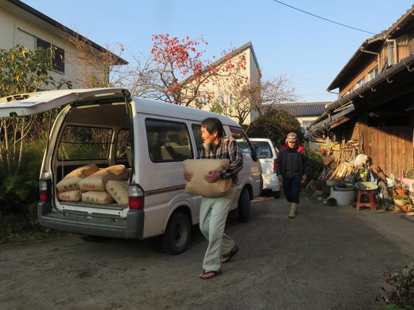 שינגו ובן דודו מעמיסים שקים של אורז, שיסיפקו למשפחה בת שבע נפשות למשך שנה