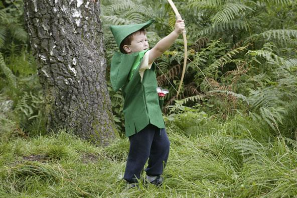 ילד בתחפושת רובין הוד יורה בחץ וקשת ביער שרווד