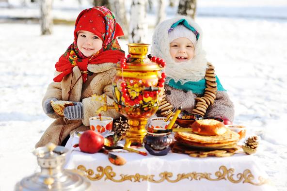 ילדות מול שולחן עמוס בכל טוב במהלך חגיגות השרובטידה, הנחגגות במזרח אירופה
