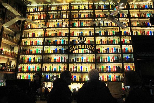 מאות בקבוקי הליקר שמכסים קיר שלם יוצרים מסך ססגוני ונעים לעין