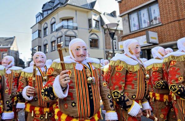 תהלוכה בקרנבל של בנש. המשתתפים לובשים בגדים כצבעי דגל בלגיה ועוטים מסכות בעלות הבעה זהה