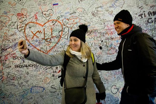 סלפי ליד קיר עם הכרזות אהבה של מבקרים מכל העולם