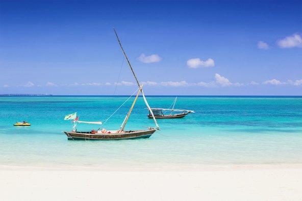 חוף בזנזיבר. חול לבן, ים טורקיז וסירות עץ כתוספת ציורית