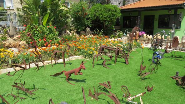 הגינה הקדמית בגלריה של סבא. זהו רק קומץ קטן מהיצירות של ניסים לוי | צילום: רותם בר כהן