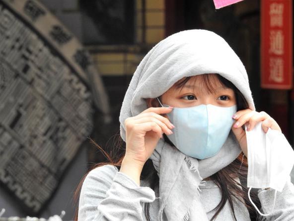 אישה עם מסכה. המסכה נועדה להגן על הלובש ועל אלה המצויים בקרבתו.