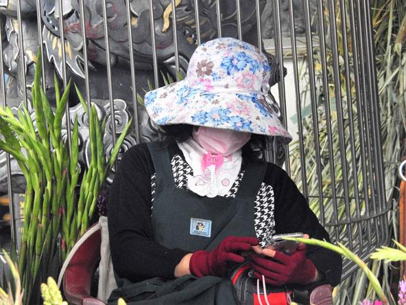 אישה עם כובע פרחוני ומסכה מסמסת. טייוואן משלבת מודרניות עם מסורת באופן חנני במיוחד