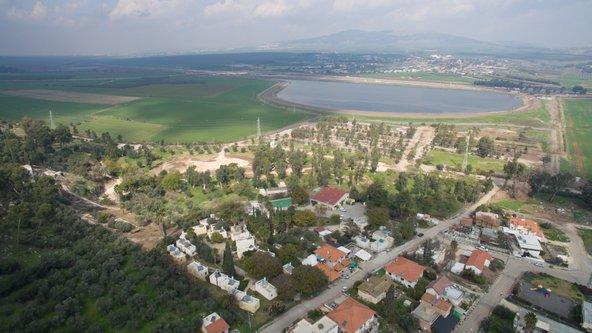 """צילום אווירי של אכסניית אנ""""א מעיין חרוד המוקפת בנופים פסטורליים"""