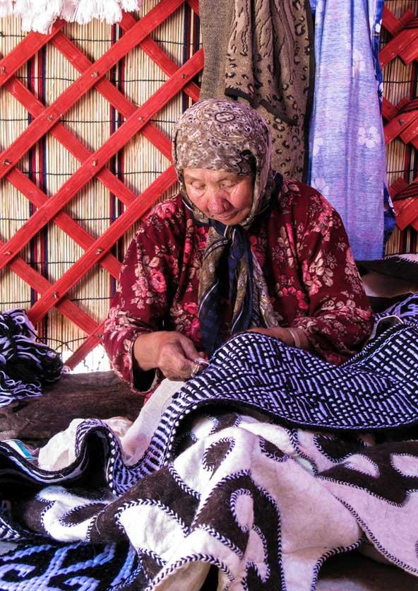 בתוך היורטה, אישה רוקמת על שמיכת צמר