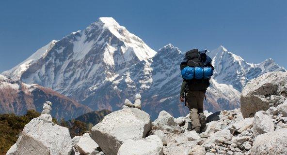 מטייל מול הפסגות רבות ההוד של ההימלאיה בשביל ההימלאיה הגדול בנפאל