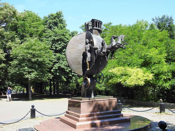 פסל של הצאר הצעיר עומד בתוך תפוז-מרכבה רתומה לסוסים, ובידו תפוז קטן