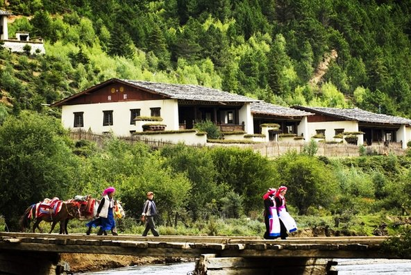 תושבים מקומיים חוצים גשר ליד מלון Banyan Tree Ringha