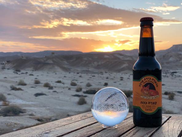 קצרה כהה של מבשלת בירה ערבה על רקע נופי המדבר בצוקים | צילום: אביעד בר