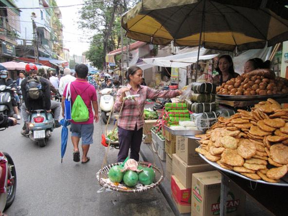 שוק בעיר העתיקה של האנוי. ערבוביה עליזה של מוכרים, טוסטוסים ואוכל
