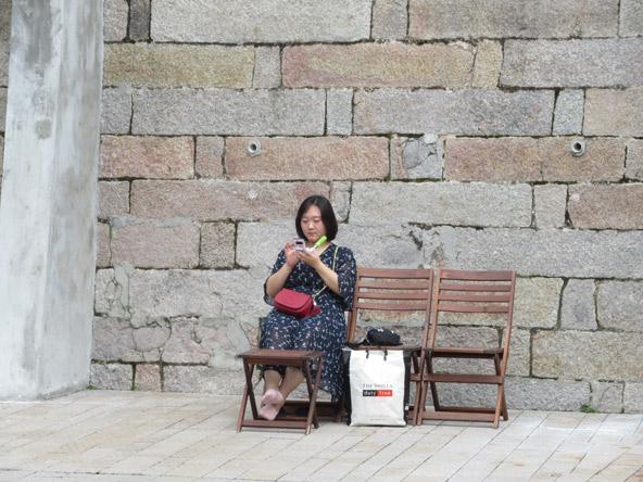 מבקרת במרכז התרבות והאמנות Tai Kwun נחה ליד חומת בית הסוהר לשעבר