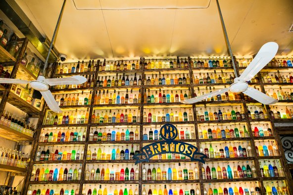 קיר עמוס בבקבוקי ליקר צבעוניים ב-Brettos