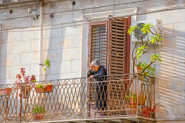 אישה לבושה בשחורים על מרפסת בפלרמו