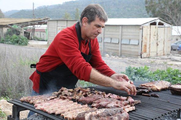 אבי מנפלאות הגריל הארגנטינאי מטפל בבשר