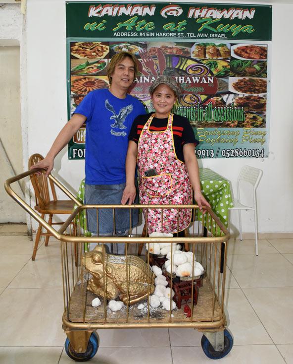 שיראל ואהרון במסעדה שלהם, לצד העגלה שבה הכל התחיל