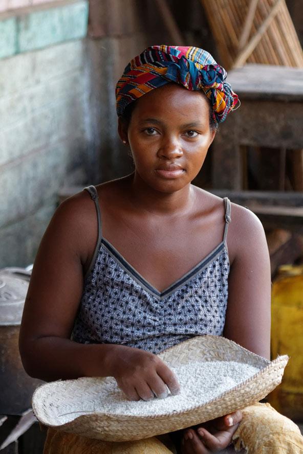נערה מלגשית עם מגש אורז. אורז הוא מרכיב מרכזי בתזונה המקומית