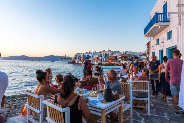 תיירים בטברנה במיקונוס | צילום: Stavros Argyropoulos / Shutterstock.com