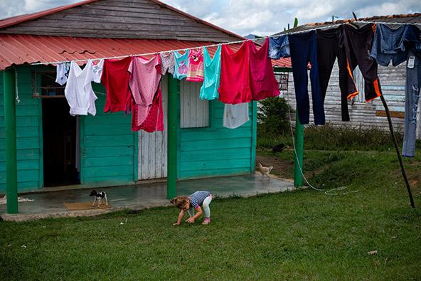 ילדה, תרנגולת וכלב. חיי כפר באיזור החקלאי. פאתי ויניאלס | צילום: אורית גוטרבוים-פרטוק