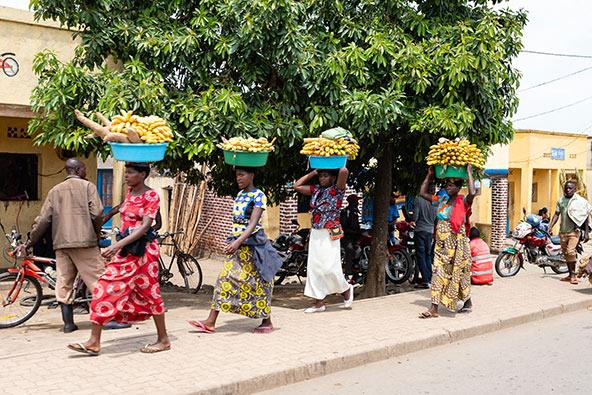 בצדי הדרכים אנשים הולכים ברגל, נושאים (לרוב על הראש) משאות כבדים