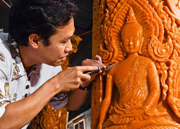 לקראת פסטיבל הנרות, אומן מגלף את דמותו של בודהה על נר שעווה גדול