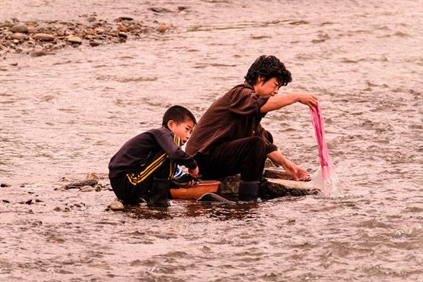 אישה כובסת בנהר יאלו בצפון קוריאה. הבידוד והסגירות הביאו בעקבותיהם עוני גדול