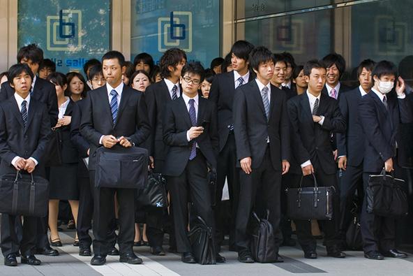 אנשי עסקים צעירים בדרכם לעבודה. קוד הלבוש המסורתי מחייב חליפה לפגישות עסקיות