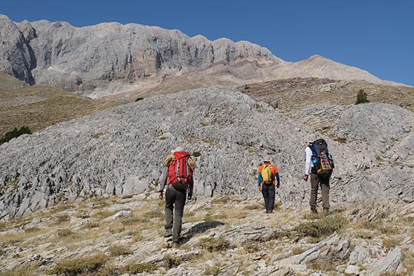 צעירי מועדון המערות של אנטליה בחציית שדה טרשים. חיפוש המערות בהרים דורש שיטוט אקראי, בתוואי שטח תלול, עם ציוד רב לירידה למעמקים