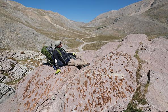 עמרי נח לצד מקבץ מאובני ספוגים, בתצפית על העמק בו התמקמה המשלחת