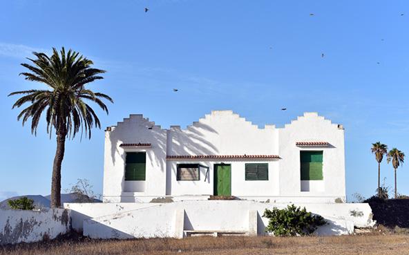בית מסורתי באי לנזרוטה. סזאר קרא לשמור על האדריכלות הקנרית המסורתית: בתים חד קומתיים צבועים לבן עם דלתות וחלונות בכחול או ירוק