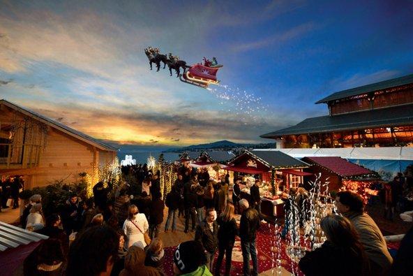 המבקרים בשוק חג המולד של מונטרה מתפעמים אל מול המזחלת של סנטה קלאוס המעופפת בשמי העיר | צילום: ©2014,studio edouard curchod