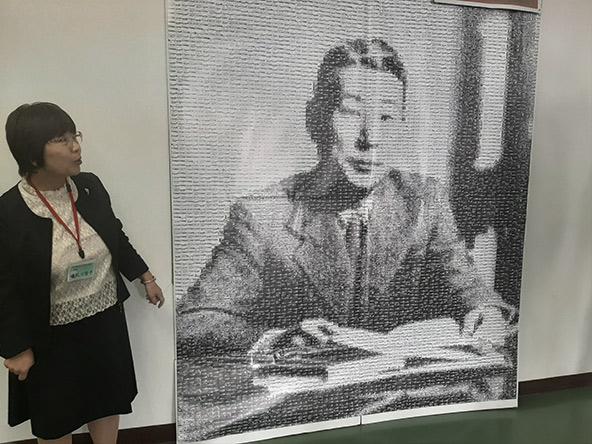 מנהלת בית הספר היסודי Heiwa בנגויה לצד עבודת יצירה ענקית שהכינו התלמידים בדמותו של סוגיהארה