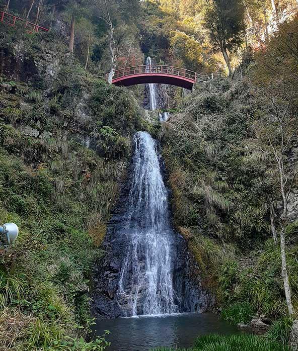 סדרת מפלים וגשר עץ אדום בשמורת טבע ליד יאוטסו. כמו ציור יפני