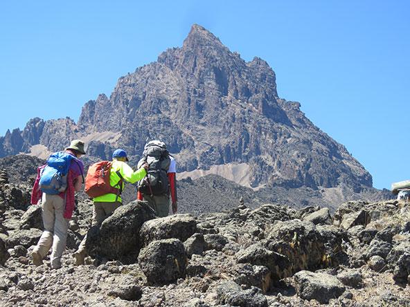 ראובן (במעיל צהוב) אוחז בתיק הגב של המדריך בדרך לפסגה