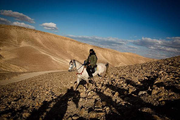בדואי על סוס צופה במשתתפים (הצלליות בקדמת התמונה) בפעילות להחייאת בור מים במדבר | צילום: דן פרברוף