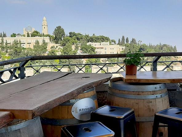 מתחם טחנת הקמח. אין כמו לשבת עם כוס יין מיקב ירושלים אל מול הנוף של גיא בן הינום והעיר העתיקה