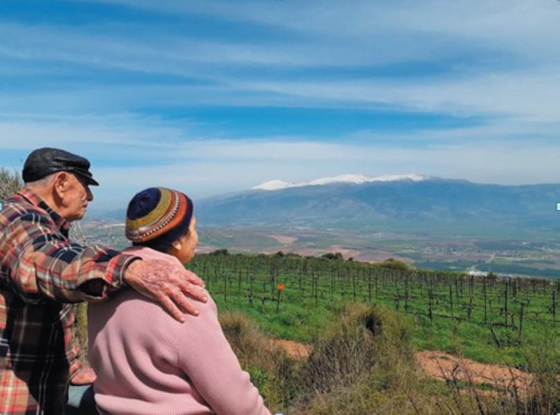 רחל (סגל) ושמוליק רבינוביץ מול החרמון במקום בו חלם קורצ'אק להקים את בית היתומים שלו, מעל קיבוצם כפר- גלעדי. צילום: מיריק שניר
