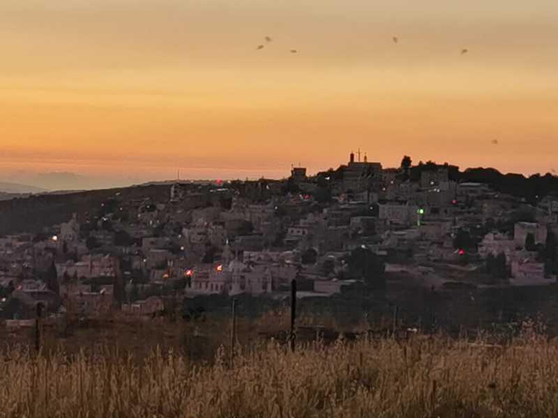 הנוף הפסטורלי של הר מירון נשקף ממול, וגגות הבתים היורדים במדרון ההר אל העמק מתחת